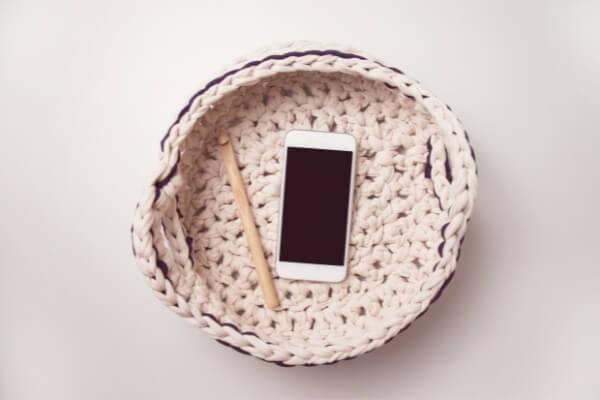 cesta de trapillo en color blanco con un teléfono móvil y na aguja de crochet
