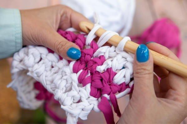 mujer tejiendo alfombra de trapillo de algodón